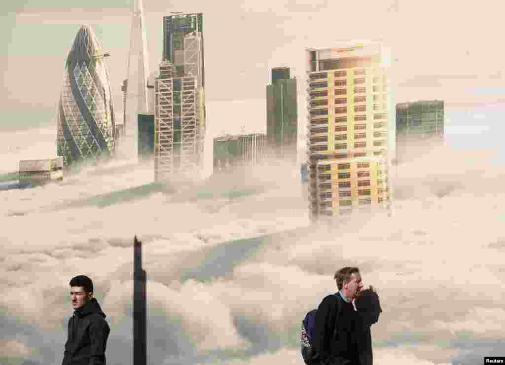 در يک روز آفتابی بهاری عابران از برابر تصوير شهر در مه میگذرند - ۲۵ فروردين ۱۳۹۴ (۱۴ آوريل ۲۰۱۵)