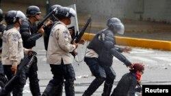 Una manifestante es capturada por la policía.