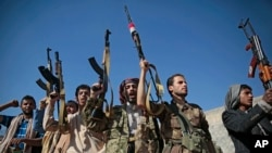 Tribesmen loyal to Houthi rebels hold up their weapons as they attend a gathering to show their support for the ongoing peace talks being held in Sweden, in Sanaa, Yemen, Dec. 13, 2018.