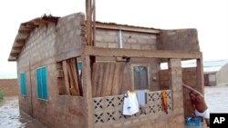 Mtu akitoka kwenye nyumba yake iliyojaa maji huko Accra region.