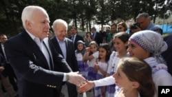 Thượng nghị sĩ Mỹ John McCain (trái) và Joseph Lieberman được các trẻ em tị nạn Syria chào đón trong chuyến thăm của họ đến trại tị nạn Yayladagi ở biên giới Thổ Nhĩ Kỳ-Syria, 10/4/2012
