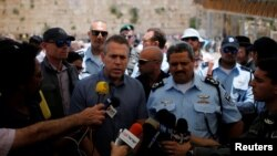 FILE - Israel's Public Security Minister Gilad Erdan, center, and police commissioner Roni Alsheich speak to members of the media at the Western Wall in Jerusalem's Old City, June 10, 2016.