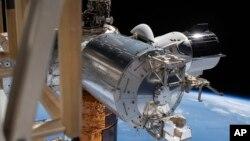 SpaceX Crew Dragon, пристыкованный к Международной космической станции, во время выхода в открытый космос