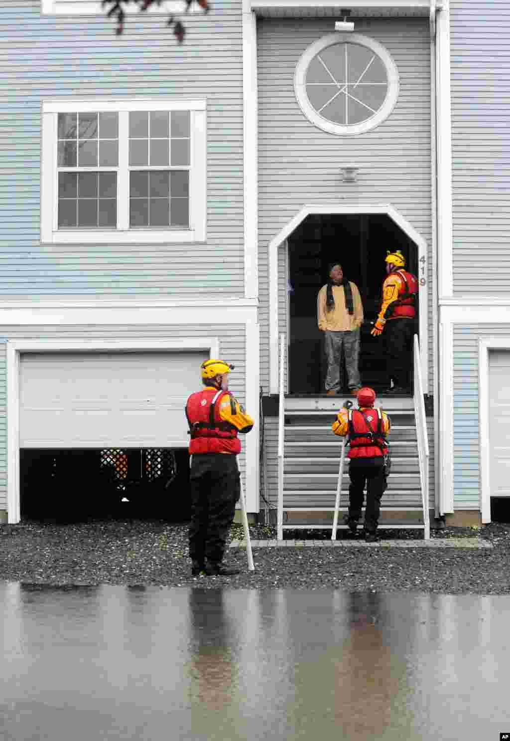 Miembros del equipo de rescate del condado de Harford en Maryland alertan a un residente para que evacúe voluntariamente su residencia después del paso de Sandy.