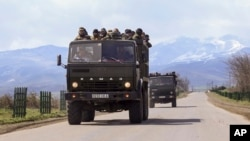 Ethnic Armenian fighters stand in backs of Kamaz military trucks on their way to a frontline at Martakert province in the separatist region of Nagorno-Karabakh, Azerbaijan, Monday, April 4, 2016.