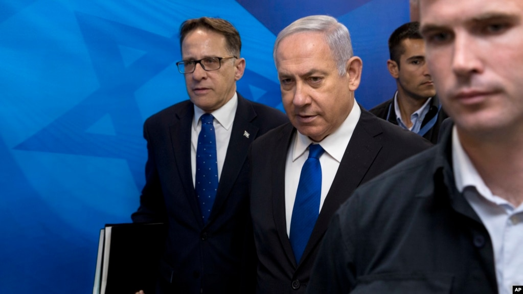 FILE - Israeli Prime Minister Benjamin Netanyahu, center, arrives with Cabinet Secretary Tzachi Braverman for a weekly Cabinet meeting at the prime minister's office in Jerusalem, April 29, 2018.