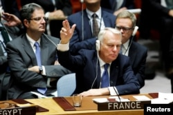 FILE - France's Foreign Minister Jean-Marc Ayrault votes in favor of a draft resolution that demands an immediate end to airstrikes and military flights over Syria's Aleppo city, during a meeting of Members of Security Council at the U.N. Headquarters in New York, Oct. 8, 2016.