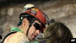 In this photo released by the Chilean government, miner Florencio Avalos, second left, hugs a relative after he was rescued from the collapsed San Jose mine near Copiapo, Chile, early Wednesday, 13 Oct. 2010