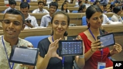 Students display Aakash, which means sky in Hindi, dubbed the world's cheapest tablet computer, after its launching ceremony in New Delhi, India, October 5, 2011.