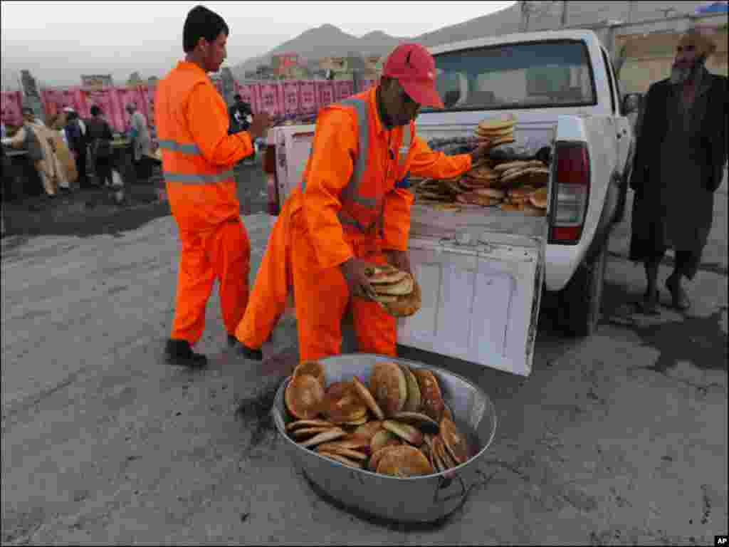 Afghan men unload bread from a vehicle as they prepare for the breaking of fast during Ramadan, the holiest month in the Islamic calendar, at a mosque in Kabul.