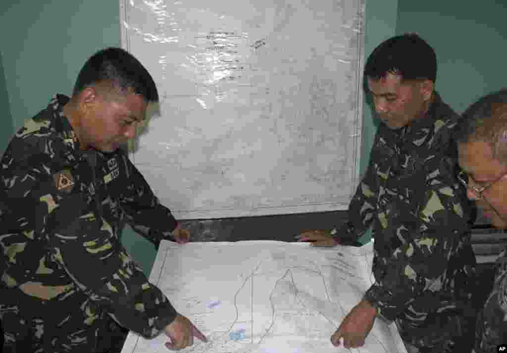 In this photo released by the Armed Forces of the Philippines, Western Command PIO, Filipino government troopers look at a map as they continue the search for the missing plane of Malaysian Airlines at Antonio Bautista Air Base in Puerto Princesa City, Palawan province.