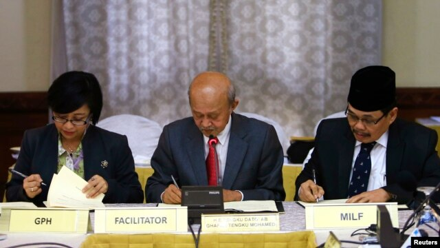 Government of the Philippines (GPH) chief negotiator Miriam Coronel Ferer (L) and Moro Islamic Liberation Front (MILF) chief negotiator Mohagher Iqbal (R) sign the peace agreement between both parties with AB Ghafar Tengku Mohamed as a witness from Malays