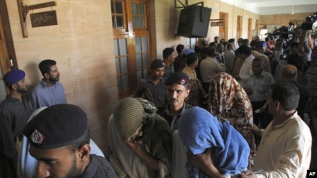 Pakistani police officers escort security officials with their faces covered, who were allegedly involved in the killing of a boy, to a police van at a local court in Karachi, June 13, 2011.