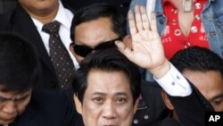 "Arisman Pongruangrong, a ""Red Shirt"" hard core leader waves as he leaves the Department of Special Investigation office to the Attorney General office at the Department of Special Investigation in Bangkok, Thailand, December 7, 2011."