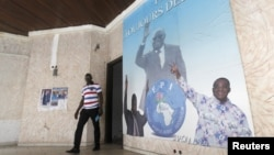 A man walks near a poster showing portraits of former Ivory coast president Laurent Gbagbo (C) and Former Ivory Coast prime minister Pascal Affi N'Guessan (R), leader of Ivorian Popular Front (FPI) at the FPI headquarters in Abidjan, September 2, 2015.