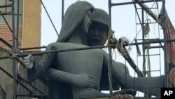 "Egypt Offensive Sculpture: A sculpture, titled ""Mother of the Martyr,"" depicts a slender peasant woman, a traditional artistic representation of Egypt, with her arms outstretched with a helmeted soldier standing behind her, at a public square in Sohag, Eg"