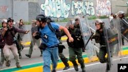 El reportero fotográfico de Reuters, Marco Bello, corre mientras los soldados de la Guardia Nacional venezolana lo persiguen durante una protesta frente a la Corte Suprema en Caracas, Venezuela, el 31 de marzo de 2017.