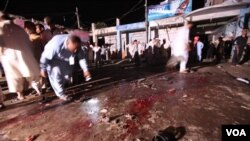 Petugas keamanan Pakistan mengumpulkan bukti-bukti di lokasi ledakan bom di Risalpur, dekat Peshawar (25/8). Ledakan bom sepeda ini menewaskan 11 orang dan merusak beberapa toko dan hotel di dekatnya.