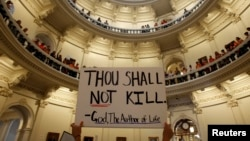 An anti-abortion protester raises a placard in the rotunda of the Texas State Capitol in Austin in this July 12, 2013, file photo.