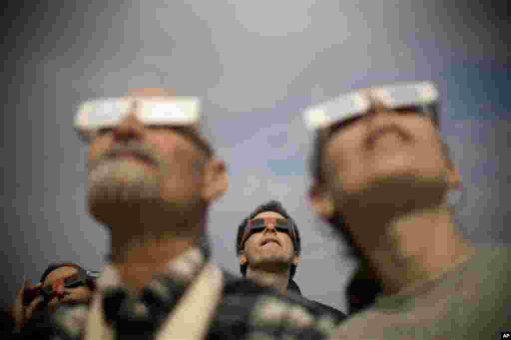 Jan 4: Israelis watch a partial solar eclipse in the town of Givatayim near Tel Aviv, Israel. A partial solar eclipse began Tuesday in the skies over the Mideast and will extend across much of Europe (Ariel Schalit/AP)