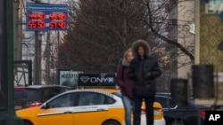 People pass by a display with exchange rates in downtown Moscow Nov. 10, 2014.