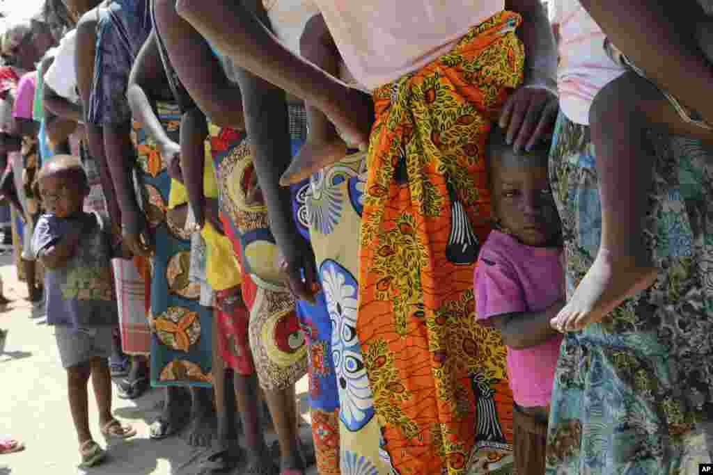 Women and children wait in a queue for oral cholera vaccinations, at a camp for displaced survivors of Cyclone Idai in Beira, Mozambique.