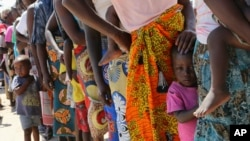 FILE - Women and children wait in a queue for oral cholera vaccinations, at a camp for displaced survivors of cyclone Idai in Beira, Mozambique, April 3, 2019.