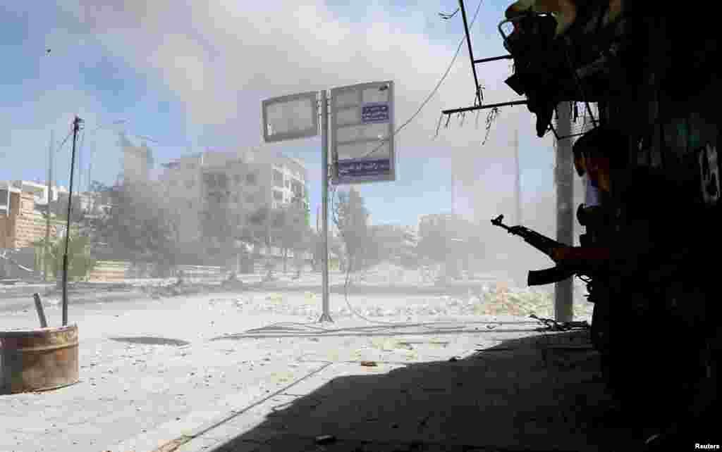 Một chiến binh phe nổi dậy chạy vào chổ núp sau tiếng nổ dữ dội trong quận Seif El-Dawla của Aleppo, 22/8/12