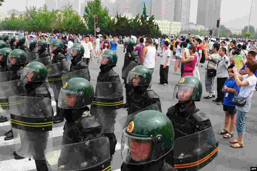 Nhiều người chụp ảnh các công an được huy động để giải quyết cuộc biểu tình đòi đóng cửa nhà máy hóa dầu Đại Liên ngày 14 tháng 8. (Reuters)