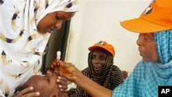 A World Health Organization official gives a dose of polio vaccine to a Somali child in Mogadishu, Sep 2006 (file photo)