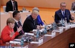 La canciller alemana Angela Merkel durante las declaraciones de apertura de la Cumbre del G20, en Hamburgo, Alemania. A su lado, el presidente chino Xi Jinping, el presidente de EE.UU. Donald Trump, la primera ministra de Gran Bretaña Theresa May y el presidente de Turquía Recep Tayyip Erdogan.