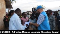 Au centre de réception de Mussungue, dans le nord-ouest de l'Angola, des employés du HCR distribuent des vivres aux réfugiés congolais ayant fui une éruption de violence dans la région du Kasaï. (UNHCR / Adronico Marcos Lucamba)