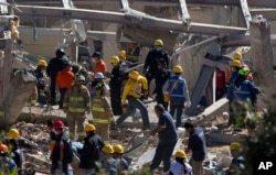 Rescue workers comb through the rubble of a children's hospital on the outskirts of Mexico City, Jan. 29, 2015.