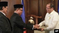 15일 마닐라 대통령궁에서 열린 서명식에서 악수하는 베니그노 아키노 필리핀 대통령(오른쪽)과 무라드 에브라힘 모로이슬람해방전선 지도자.