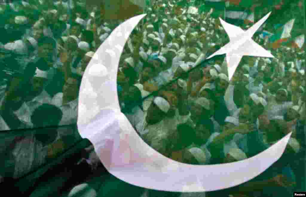Muslim demonstrators are seen through a flag as they shout anti-U.S. slogans during a protest in Chennai, September 18, 2012.