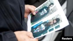 Một nhân viên cảnh sát Đức cầm tấm ảnh của một nghi can khủng bố trước mặt tiền phi trường Berlin-Schoenefeld ở Schoenefeld, gần Berlin ngày 9/10/2016.