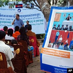 Khmer Rouge Tribunal spokesman Lars Olsen speaking to former members of the ultra-Maoist group in Anlong Veng, Cambodia at the home of Ta Mok, a former senior leader believed to have been responsible for many of the regime's worst atrocities. The poster o