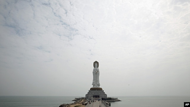 Tourists walk towards a 108-meter high Buddhist statue at Nanshan Cultural Center, about 60km (37 miles) west of Sanya, in south China's Hainan Island province. (file photo)