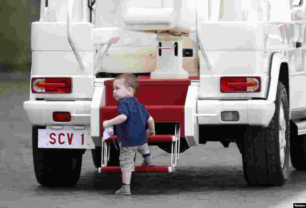 A child climbs up the Pope mobile as Pope Francis leads his general audience in San Peter's square at the Vatican.