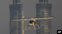 FILE - A Volocopter prototype flies in front of the two hotel towers during a test flight of pilotless taxis in Dubai, United Arab Emirates, Sept. 26, 2017. The ride-hailing company Uber says, Nov. 8, 2017, it has signed a deal with the U.S. space agency NASA to develop a fleet of flying vertical takeoff and landing taxis by the end of the decade.