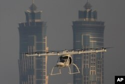 FILE - A Volocopter prototype flies in front of the two hotel towers during a test flight of pilotless taxis in Dubai, United Arab Emirates, Sept. 26, 2017.