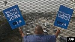 """Stanovnik Los Andjelesa nosi transparent na kojem piše: """"Trebaju nam dobra radna mesta"""""""