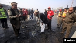 19일 파키스탄 페샤와르 시 검문소에서 자살폭탄 공격이 발생한 후 치안 관계자들이 사건 현장을 수색하고 있다.