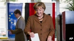 German Chancellor Angela Merkel, chairwoman of the Christian Democratic party CDU, casts her vote in Berlin, Sunday, Sept. 22, 2013. 62 million voters in Germany are entitled to elect a new parliament as Merkel runs for her third term as chancellor. In th