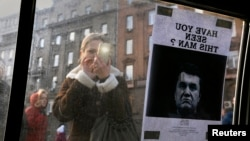 """A woman takes a photo of a """"Wanted"""" notice for fugitive Ukrainian president Viktor Yanukovych, plastered on the window of a car near Kyiv's Independence Square Feb. 24, 2014."""