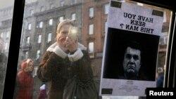 Một phụ nữ chụp ảnh lệnh 'truy nã' Tổng thống Victor Yanukovich tại Kiev.