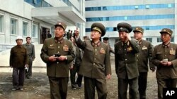 북한 권부의 실세로 부상한 최룡해(중앙) 총정치국장의 개건부수전투장 시찰 장면(자료사진)