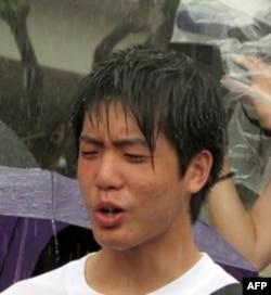 一位年轻人不畏倾盆大雨参加集会