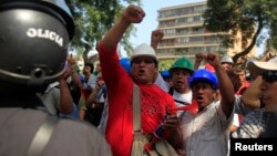 FILE - Mining workers of Doe Run Peru protest in front of the Labor Ministry in Lima to demand that Peru's government save their jobs at the shuttered La Oroya metals smelter in the Andes, April 19, 2012.