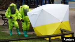 FILE - The forensic tent, covering the bench where Sergei Skripal and his daughter Yulia were found, is repositioned by officials in protective suits in the center of Salisbury, Britain, March 8, 2018.